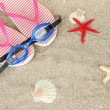 Stock Photo: Composition with flip flops, goggles on sand background