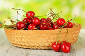Cherry berries in wicker basket on wooden table on bright background — Stock Photo