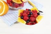 Useful fruit salad in glass cup and bowl on wooden table close-up — Stock Photo