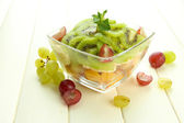 Tasty fruit salad in glass bowl, on white wooden table — Foto de Stock