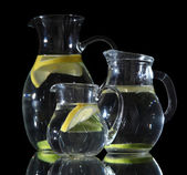 Glass pitchers of water isolated on black — Stock Photo