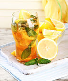 Iced tea with lemon and mint on wooden table — Stock Photo