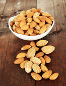 Almond in bowl, on wooden background — Stock Photo