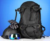 Occhiali sportivi invernali, casco e guanti, zaino, su sfondo blu — Foto Stock