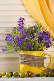 Beautiful bouquet of wildflowers in cup and berries on wooden table — Stockfoto