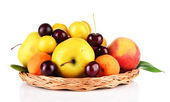 Bright summer fruits in basket isolated on white — Stock Photo