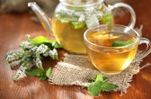 Cup and teapot of herbal tea with fresh mint flowers on wooden table — Stock Photo