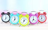 Masanın üzerine ışık arka plan üzerinde renkli çalar saatler — Stok fotoğraf