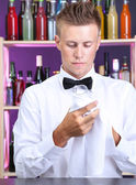 Bartender wipes glasses at work — Stock Photo