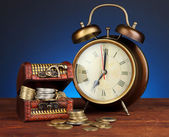 Reloj antiguo y las monedas en la mesa de madera sobre fondo de color oscuro — Foto de Stock