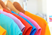 Variety of casual t-shirts on wooden hangers on shelves background — Foto de Stock