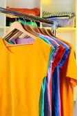 Verscheidenheid van casual t-shirts op houten hangers op planken achtergrond — Stockfoto