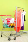 Shopping cart with clothing, on color wall background — Stok fotoğraf
