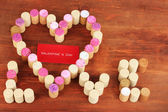 Wine corks laid out in form of heart on wooden table close-up — Stock Photo