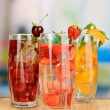Glasses of fruit drinks with ice cubes on table in cafe — Stock Photo