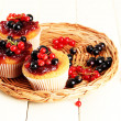 Tasty muffins with berries on white wooden table — Stock Photo #29531997