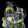 Stock Photo: Glass pitchers of water isolated on black