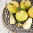 Pears on braided tray on wooden table — Stock Photo #29533485