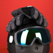 Winter sport glasses, helmet and gloves, on red background — Stock Photo