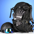 Winter sport glasses, helmet and gloves, backpack, on blue background — Foto Stock