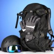 Winter sport glasses, helmet and gloves, backpack, on blue background — Stock Photo #29533623