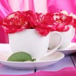Roses in cups on wooden table on pink cloth background — Stock Photo