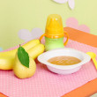 Tasty baby fruit puree and baby bottle on table in room — Stock Photo