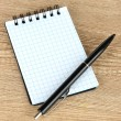 Stock Photo: Notebook and pen on wooden table