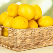 Ripe lemons in wicker basket on table on bright background — Stock Photo #29534413