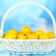 Ripe lemons in wicker basket on table on bright background — Stock Photo #29534417