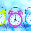 Colorful alarm clocks on table on blue background — Stock Photo #29534495