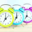 Colorful alarm clocks on table on light background — Stock Photo #29534499