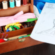 Stock Photo: Sewing kit in wooden box,cloth and sketch on wooden table