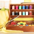 Stock Photo: Sewing kit in wooden box with books and cloth table on bright background