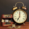Antique clock and coins on wooden table on black background — Stock Photo #29534575