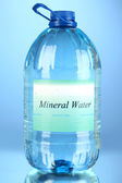 Big water bottle with label on blue background — Stock Photo