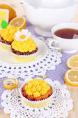 Beautiful lemon cupcakes and flavored tea on dining table close-up — Stock Photo