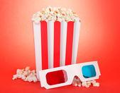 Palomitas de maíz y gafas 3d sobre fondo rojo — Foto de Stock