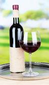 Copa de vino y la botella en el fondo brillante — Foto de Stock