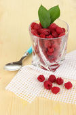 Ripe raspberries in glass on wooden table close-up — Stock Photo
