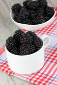 Sweet blackberries in cup on table close-up — Stock Photo