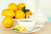 Cup of tea with lemon on table on light background — Photo