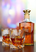 Glass of whiskey with bottle, on dark background — Stock Photo