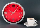 Cup coffee and clock on gray background — Stock Photo