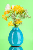 Beautiful bouquet of freesia in vase on green background — Stock Photo