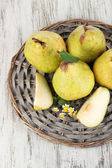 Pears on braided tray on wooden table — Stock Photo