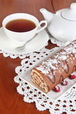 Rollo dulce con taza de té en primer plano de la mesa — Foto de Stock