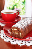 Sweet roll with cup of tea on table in room — Stock Photo