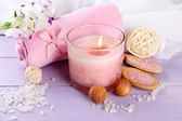 Schönes spa-einstellung mit rosa kerze und blumen auf lila hölzernen hintergrund — Stockfoto