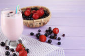 Delicious milk shake with blackberry and strawberries on wooden table close-up — Stock Photo